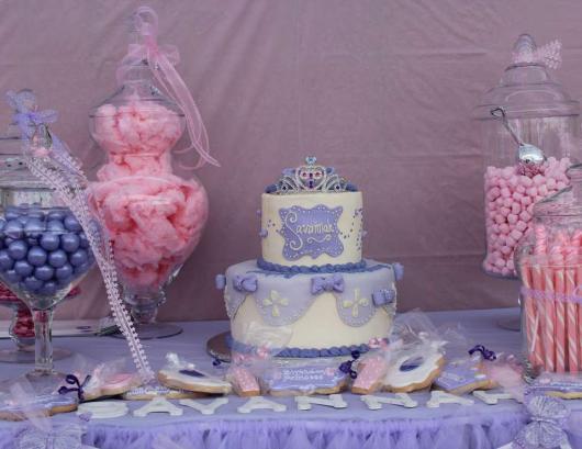 Bolo com base branca e detalhes em lilás e roxo, rodeado por bombonieres coloridas.