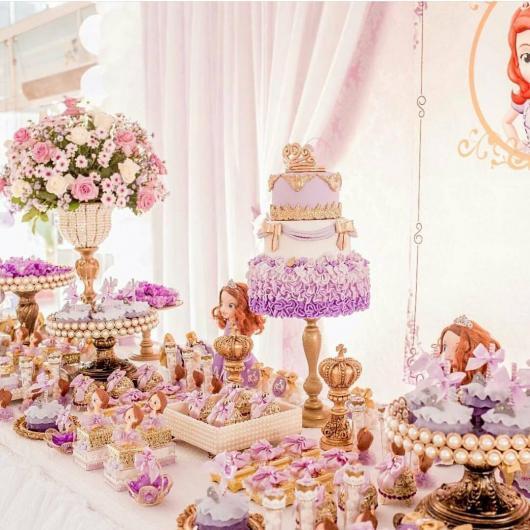 Toalhas de mesa e cortinas em tons claros de creme, branco e rosa claro, com decoração festa princesa Sofia sobre a mesa em dourado, roxo destacadas.