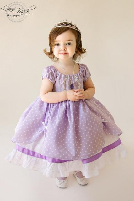 Bebê em vestido lilás e usando coroa dourada fina e colar com pedra roxa.