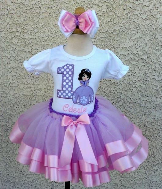 Blusa infantil branca com tutu lavanda e detalhes em fita rosa.
