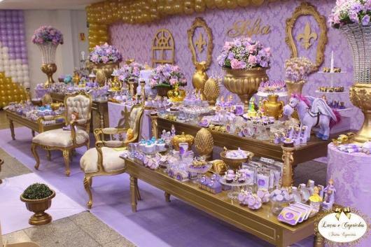 Ambiente decorado com vasos de flores, móveis e objetos dourados em abundância, combinando com o lavanda e violeta