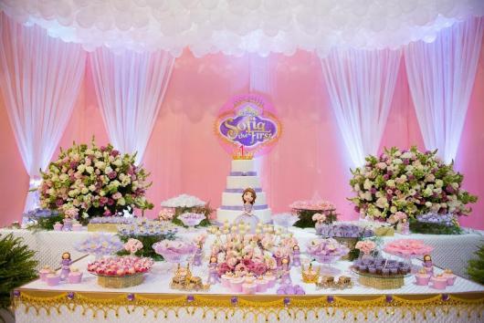 Mesa de festa princesa Sofia decorada com detalhes em rosa e lilás com fundo rosa com cortinas e bexigas brancas.