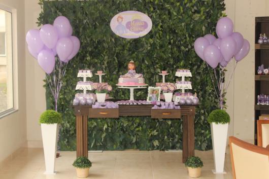 Decoração festa princesa sofia em móveis rústicos com fundo de folhas verdes entre bexigas lavanda