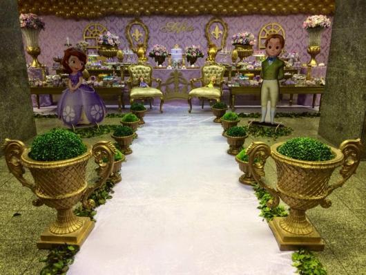 Decoração que imita o jardim de um castelo, com grama falsa, vasos dourados, bonecos em tamanho natural da princesinha Sofia e do príncipe James e imitação de tronos de um castelo