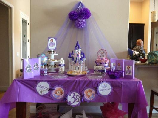 Decoração para festa princesa sofia simples, feita com papel crepom, impressões e brinquedos dispostos na mesa.