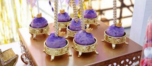 Bolo de palito revestido em roxo sobre suporte dourado que imita porta-jóias.