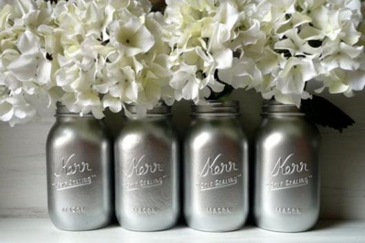 Vasos cinza com flores brancas.