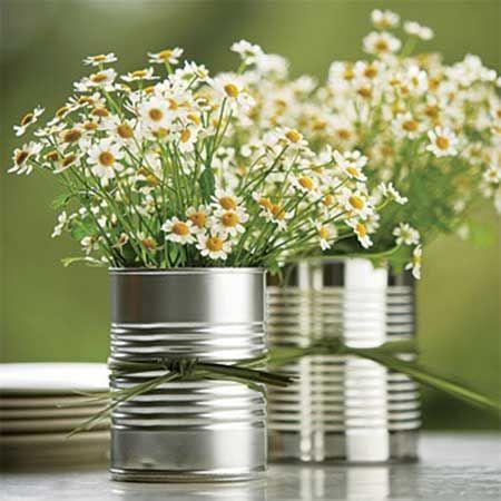 Latas servindo como vasos de flores brancas.