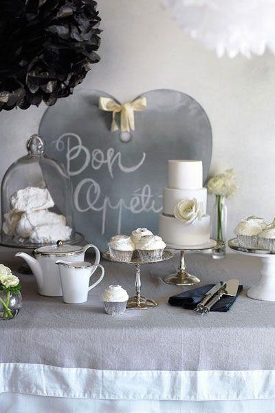 Mesa decorada com itens brancos, cinza e prata.