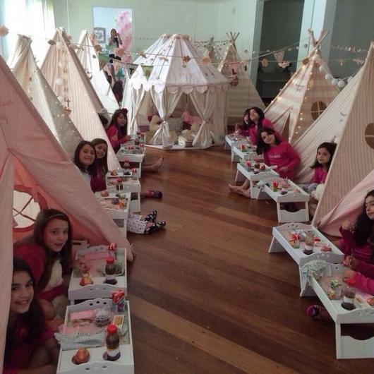 Várias meninas dentro de pequenas cabanas montadas em uma sala.