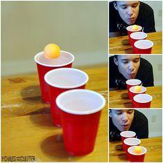 Brincadeira de soprar uma bolinha por copos de água.