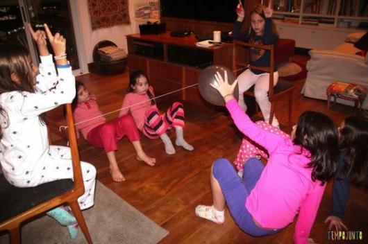 Rede improvisada na sala com crianças usando bexiga para brincar de futevôlei.
