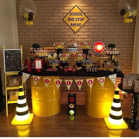Mesa de aniversário feita com latões amarelos.