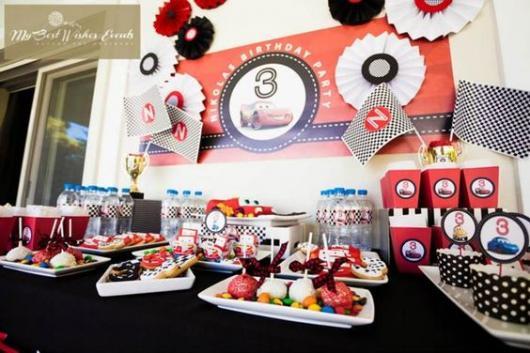 DEcoração de aniversário de três anos com toalha preta e acessórios brancos e vermelhos.