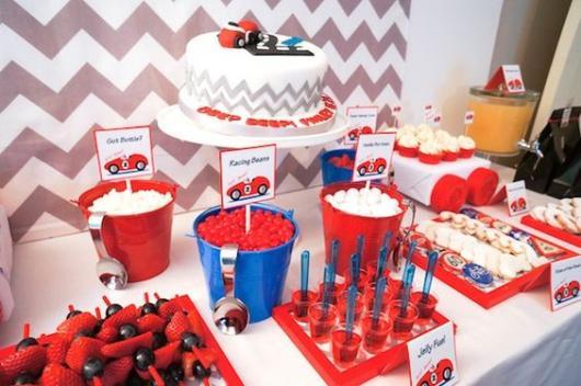 Mesa do bolo com potes grandes com guloseimas.