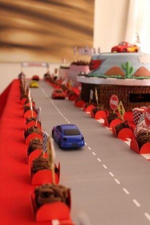 Mesa de aniversário com pista de corrida, carrinhos e brigadeiros no contorno da pista.