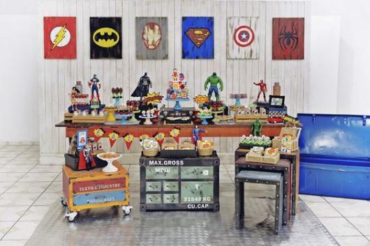Decoração com símbolos dos heróis no fundo e bonecos em cima da mesa.