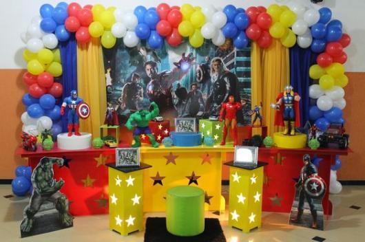 Fundo da mesa com imagem dos Vingadores e móveis vermelhos e amarelos.