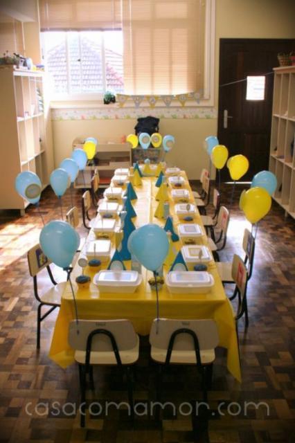 Mesas de escola juntas, com toalha amarela e bexigas.
