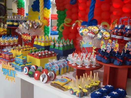 Decorações com balões e suportes de docinhos coloridos.