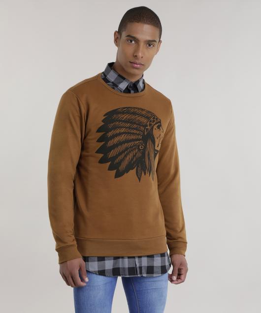 Homem com blusa marrom com desenho de índio e camisa xadrez por baixo.