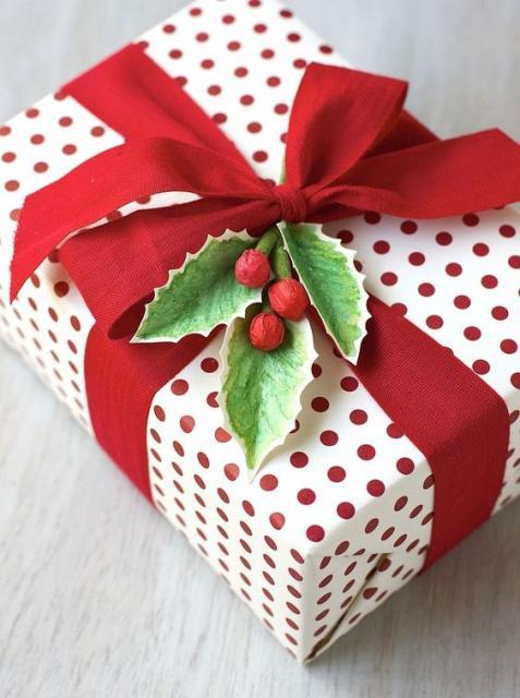 Embrulho com papel branco com bolinhas vermelhas e fita vermelha.
