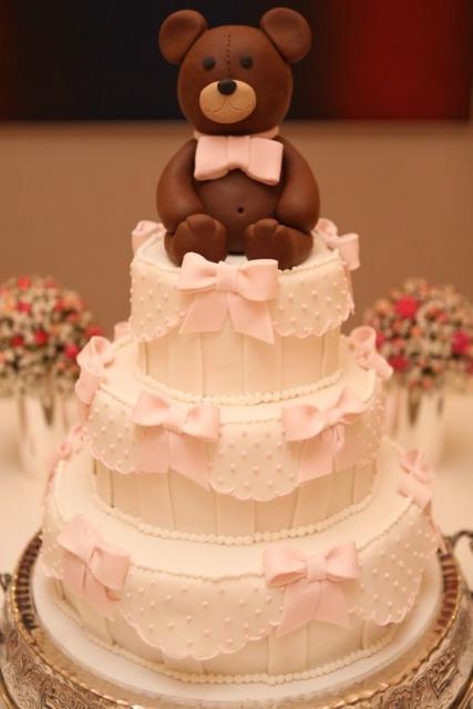 Bolo de batizado feminino com ursinho de biscuit e lacinhos decorando