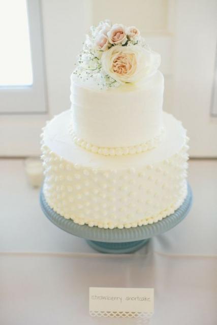 Bolo de duas camadas branco com flores em cima e pérolas na lateral.