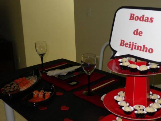 mesa com comida japonesa e beijinhos ao lado com placa de bodas de beijinho