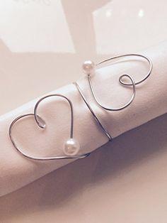 Anel de guardanapos que formam um coração com pérolas nas pontas.