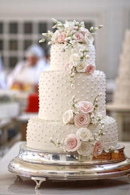 Bolo de três camadas com flores rosas e brancas e pérolas.