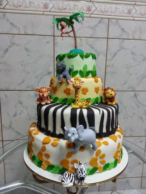 bolo fake safari de biscuit com cada animal em uma camada e um macaco em uma árvore no topo