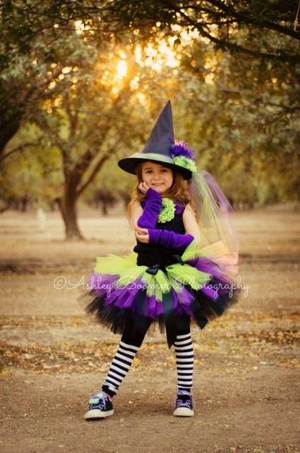 Menina vestida de bruxa, com roupa preta, roxa e verde.