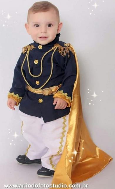 Menino vestido de príncipe, comc calça branca, blusa azul marinho e capa dourada.