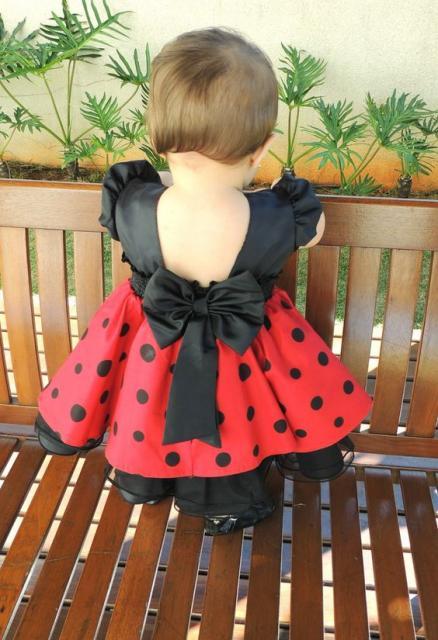 Menina de costas vestida de Minie, com blusa preta e saia vermelha com bolinhas pretas.