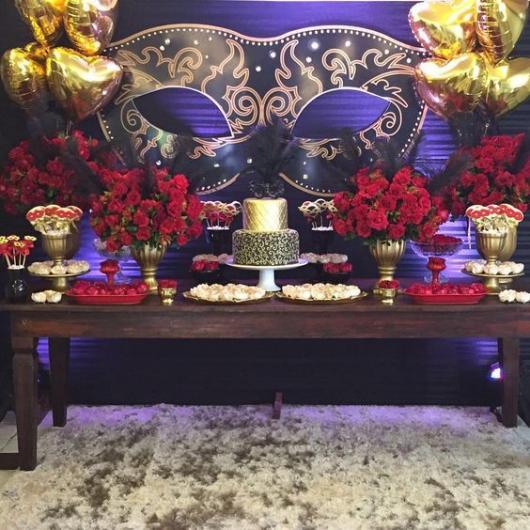 Decoração de mesa de bolo com flores vermelhas e fundo azul com máscara.