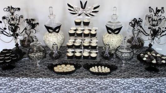Mesa de bolo com máscaras pretas e decoração branca.