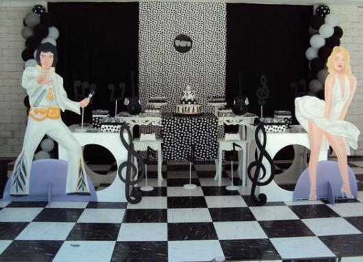 Piso quadriculado branco e preto, com imagens de personagens famosos e mesa do bolo com os mesmo tons.