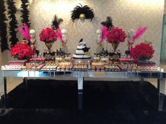 Decoração de mesa de bolo com máscaras na parede do fundo.
