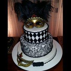 Bolo branco e preto com máscara dourada e plumas no topo.
