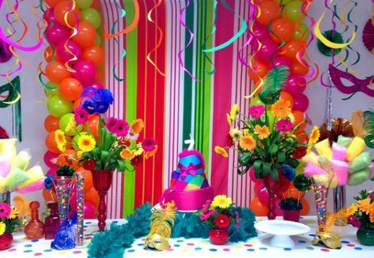 Mesa de bolo com balões, flores e serpentinas coloridas.