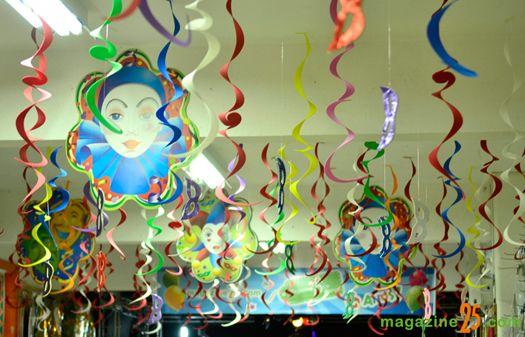 Salão de festa com serpentinas coloridas e máscaras.