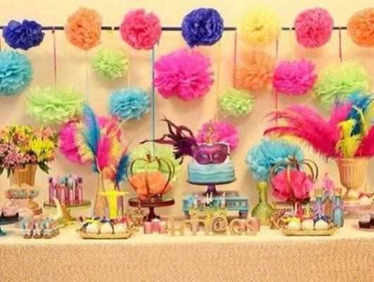 Decoração de mesa de bolo com pompons coloridos, plumas e máscaras.