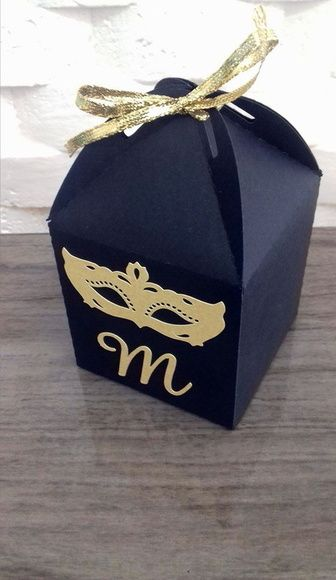 Caixinha preta de lembrancinha com máscara dourada na frente.