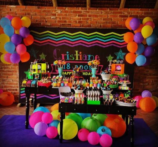 Decoração de mesa de aniversário com bexigas e itens decorativos coloridos.