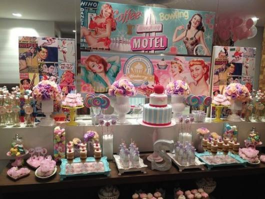 mesa de doces de aniversário pin-up, com fotos de mulheres pin-up ao fundo