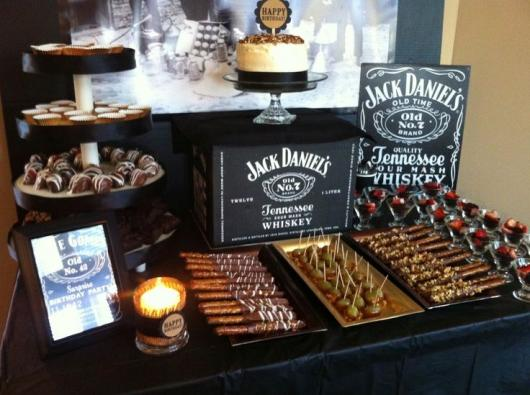 mesa do bolo com espetinhos de doce e desenhos do whisky Jack Daniel's