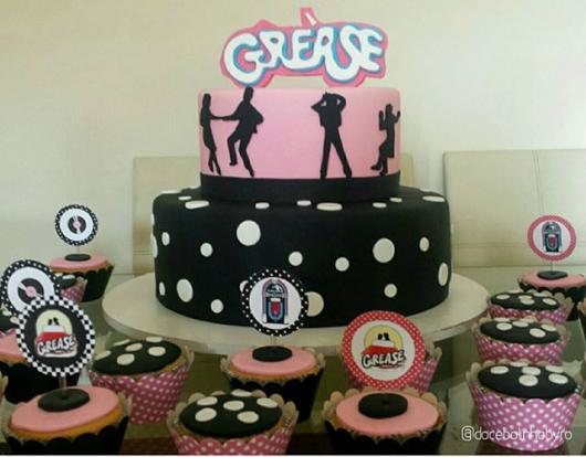 mesa de doces de aniversário com o nome Grease, bolinhas e desenhos de pessoas dançando