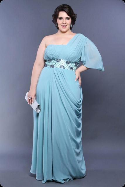Modelo usa vestido azul claro de um ombro só, acinturado com carteira de mao azul.