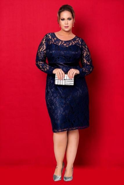 Modelo veste vestido comprimento médio azul marinho manga longa, todo em renda combinado com sandalia na mesma cor.